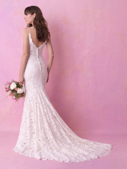 Subtle pearlescent beadwork adorns the neckline of this sleeveless lace sheath.
